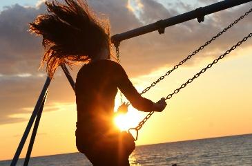 Girl swinging at sunet